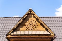 Carved wooden gable. Wooden gable and metal roof against the blue sky stock photos