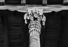 Carved wooden kapitel columns supporting a beam of overlap. Black and white view Stock Image