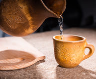 Carved Wooden Pitcher Pouring Water Into Cup Stock Photos