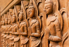 Carved wooden sculpture of praying Buddha in a line of different prayers Royalty Free Stock Image