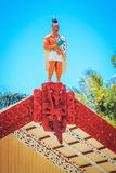 A carved wooden statue of a Maori man on top of the meeting house stock image