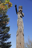 Carved wooden totem pole in riverfront park with autumn tree Stock Photo