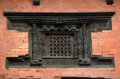 Carved wooden window on a brick wall Stock Images