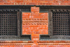 Carved wooden window on a brick wall Stock Photos