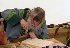 Carver of Wood. Man in Scandinavian costume doing wood carving royalty free stock photos