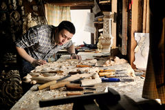 Carver in workshop of wood carving blow off sawdust Royalty Free Stock Photo