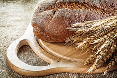 Carving board bread wheat ears on vintage hessian background.  royalty free stock image