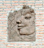 Carving of Buddha face. On the brick wall Stock Photos