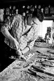 Carving with chisel monochrome image. Carver in workshop carving with chisel monochrome stock photography