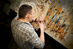 Carving with chisel ornamental objects in workshop. Carver in workshop carving with chisel to make ornamental objects Royalty Free Stock Image