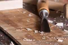 Carving chisel on workbench with wood chips stock images