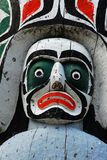 Carving face on totem pole