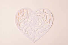 Carving heart cutted from paper on the paper background Royalty Free Stock Image