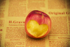 Carving heart-shaped pattern in apple Stock Photos