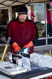 Carving ice with saw in a competition Royalty Free Stock Photos