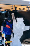 Carving ice skater in ice. A man uses a chisel to carve details into a ice sculpture of an ice skater, during a winter festival in st Joseph Michigan stock photography