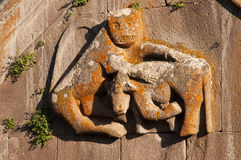 Carving of lion attacking a bull Stock Photography