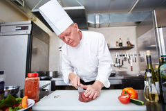 Carving meat. Chef carving meat at the kitchen stock photo