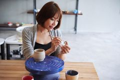 Carving mug handle. Asian young woman carving handle for her clay mug Royalty Free Stock Images