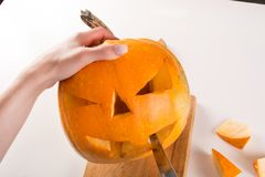 Carving orange pumpkin for Halloween holiday royalty free stock image