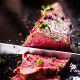 Carving a portion of rare roast beef. Carving a portion of delicious rare roast beef sirloin of fillet seasoned with fresh herbs with a large steel carving knife Stock Photography