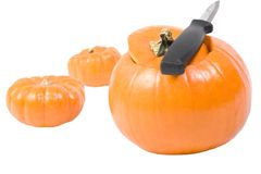 Carving the Pumpkin. Three small pumpkins and knife, one pumpkin with top removed Stock Photo