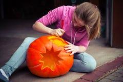 Carving pumpkin. A girl carving a pumpkin royalty free stock photography