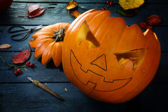 Carving a pumpkin for halloween, tinker autumn decoration on a b Stock Photography