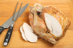 Carving Roast Chicken. Roast chicken on wooden carving board with sliced breast meat Stock Photo