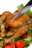 Carving a roast chicken. In a bed of lettuce and tomato salad royalty free stock photo