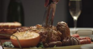 Carving roasted chicken on a festive table. Close up video of carving homemade roasted chicken with oranges and rosemary on a Christmas party table stock video footage