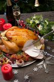 Carving Rustic Style Christmas Turkey. Carving rustic style roasted Christmas turkey garnished with roasted garlic, lemon, and rosehips. Surrounded with rustic Stock Photos