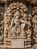 Carving of Vishnu. A carving of the Hindu god Vishnu sitting beneath a tree at the 13th Century temple of Somanathapur, Karnataka, South India stock photo