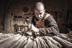 Carving wood working. Portrait of carpenter at work with hammer and gouge stock photography