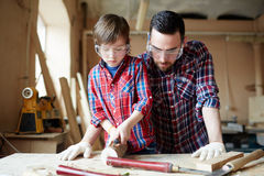 Carving wood. Youthful kid with chisel carving wooden workpiece with his father near by Royalty Free Stock Images