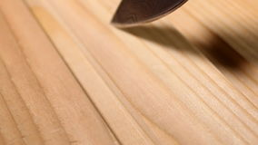 Carving on the wooden planks. Knife from damask steel. stock footage