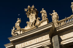 Carvings on top of Colonnades, St Peters Square, with moon. Royalty Free Stock Photos