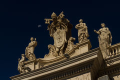 Carvings on top of Colonnades, St Peters Square, with moon. Royalty Free Stock Photography