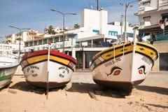 Carvoeiro,葡萄牙- 2016年12月10日, :旅游旅行的两条木传统五颜六色的美丽的木小船向海陷下 免版税库存图片