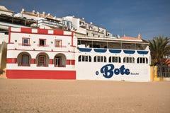 Carvoeiro, Portugal - 10. Dezember 2016: bunte traditionelle portugiesische Architekturhäuser auf sandigem Strand im blauen Himme Stockbilder