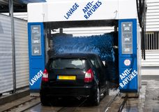 Carwash in action. French carwash in action with a black little car stock photography