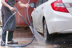 Carwash. Man Spraying to wheel a white car Stock Photography