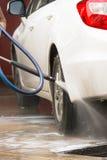 Carwash. Spraying water to a white car Stock Photos