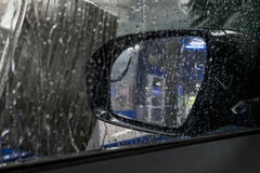 Carwash through window showing mirror Stock Photo