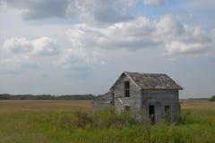 Casa abandonada da exploração agrícola com as nuvens na pradaria de Minnesota fotografia de stock royalty free