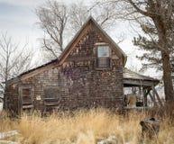 Casa abandonada da exploração agrícola com grama coberto de vegetação e nenhum s infrinjindo Fotos de Stock