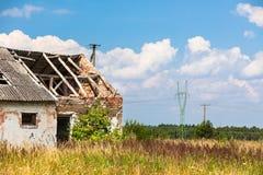 Casa abandonada de la granja en un campo Imagen de archivo libre de regalías