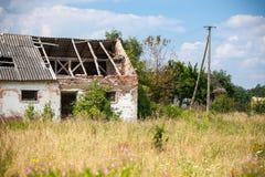 Casa abandonada de la granja en un campo Imagen de archivo