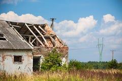 Casa abandonada de la granja en un campo Foto de archivo libre de regalías