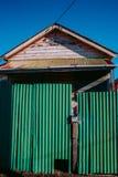 Casa abandonada detrás de la cerca verde foto de archivo